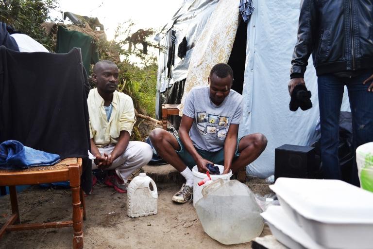Un sudanés limpia sus vaqueros mientras otro se lava las manos.